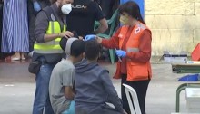 Una voluntaria atiende a varios menores no acompañados a su llegada a Ceuta el pasado mes de mayo.